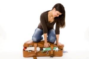 девушка собирает вещи в чемодан для путешествия в горы