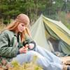 девушка сидит у походной палатки в лесу