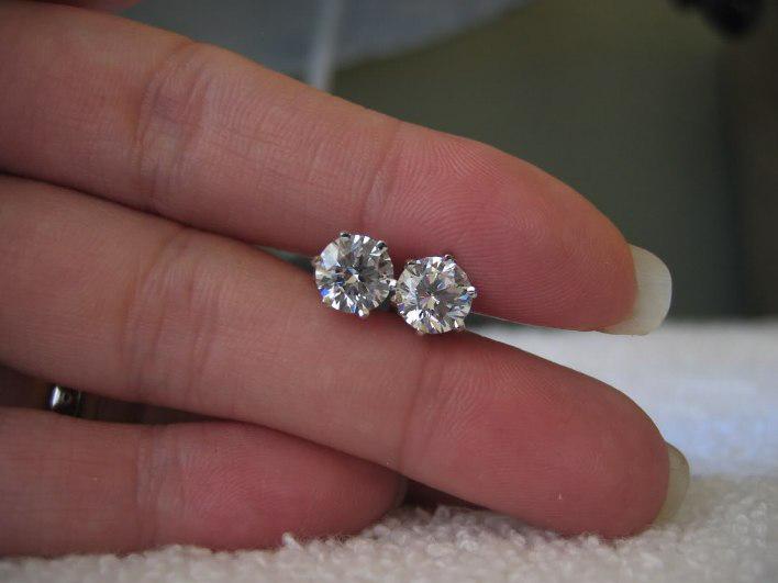 гвоздики с бриллиантами в женской руке